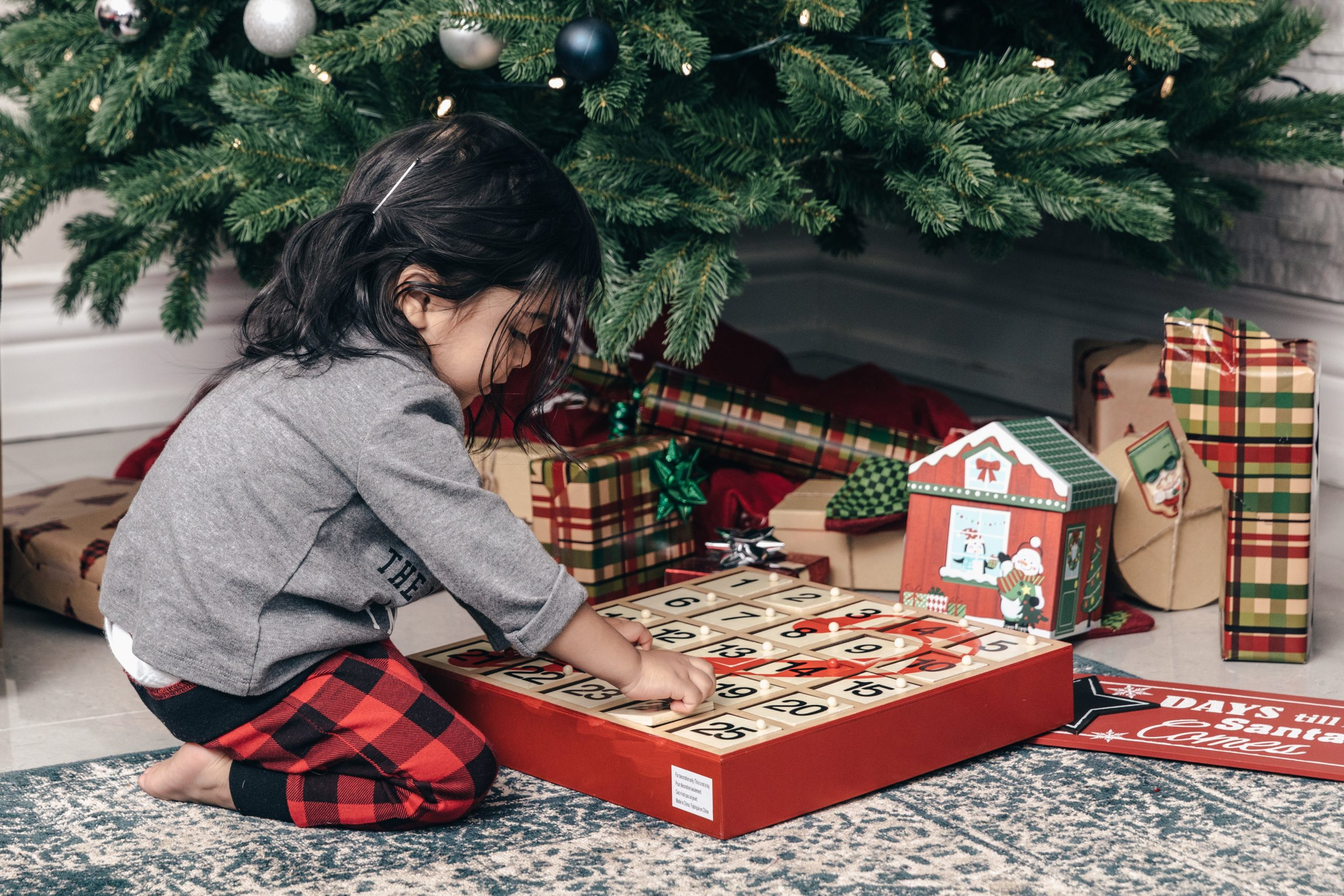 child-with-advent-calendar-under-christmas-tree